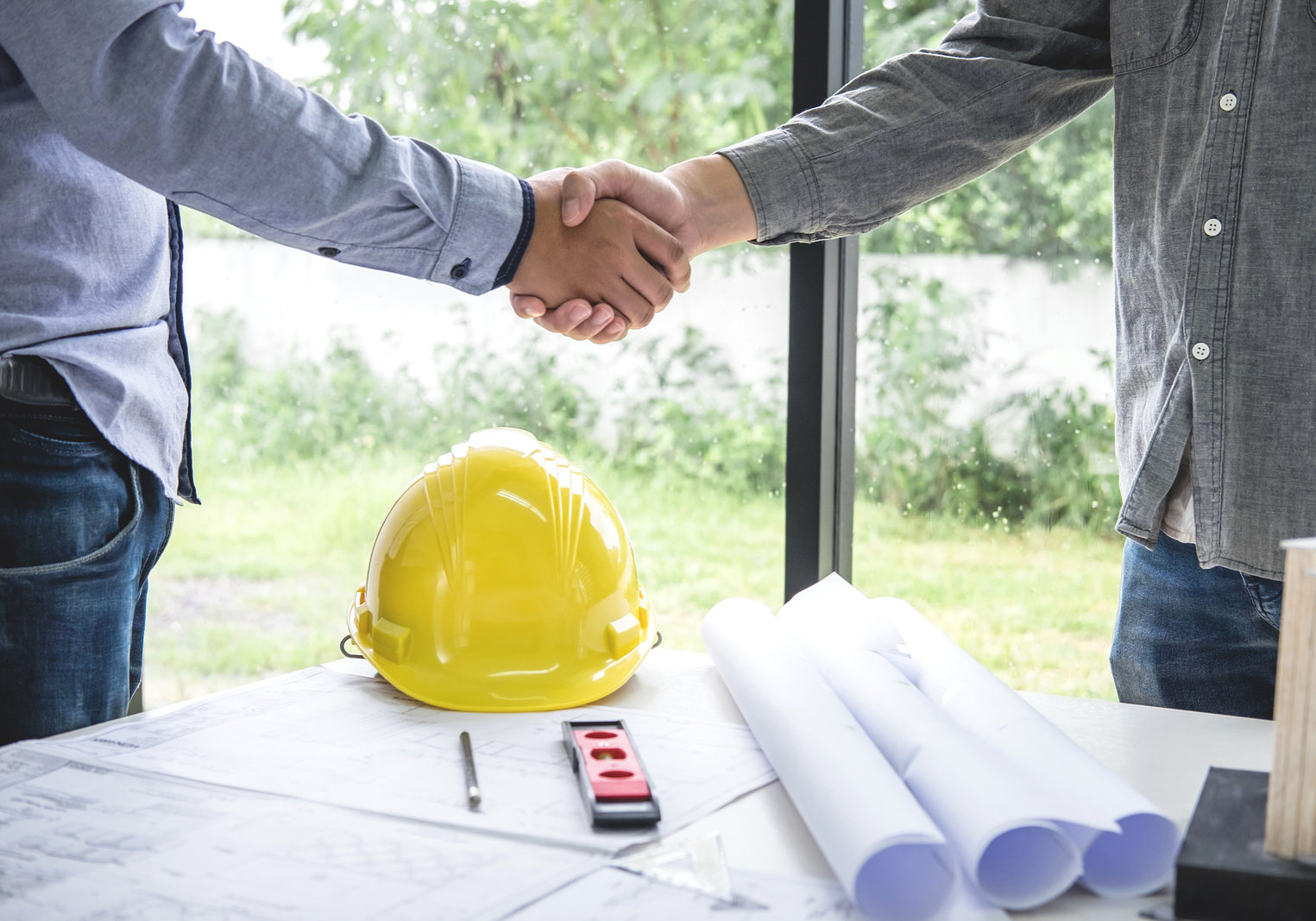 Shaking hands of collaboration, Construction engineering or architect discuss a blueprint while checking information on drawing and sketching, meeting for architectural project of partner.